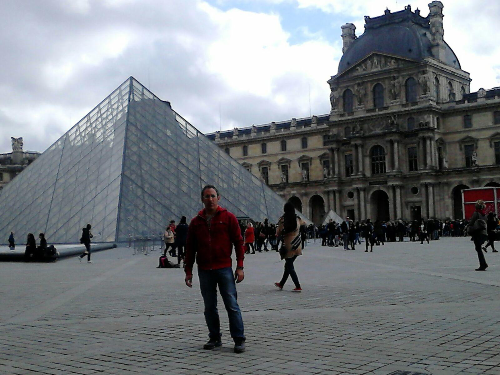 Ángel delante de una de las pirámides del Louvre en París.