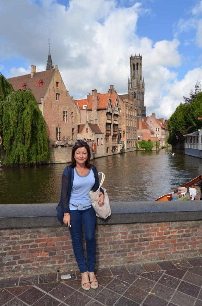 Montse en Brujas junto al muelle del Rosario y torre Belfort al fondo.