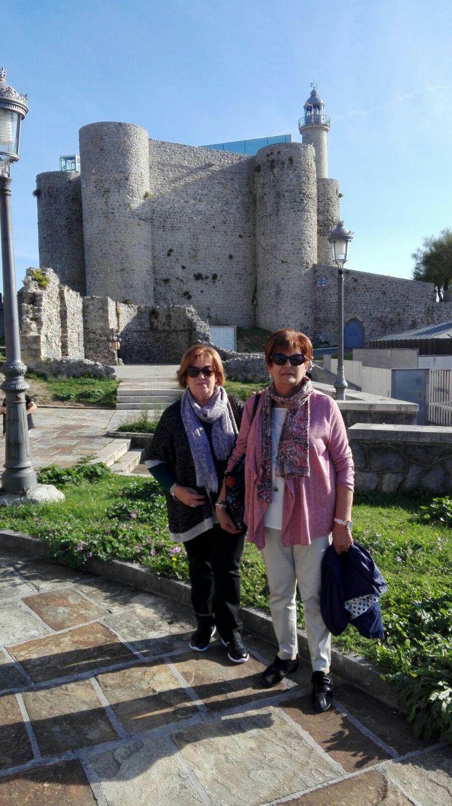Ventura y Montse con el Castillo Faro al fondo, en Castro Urdiales.