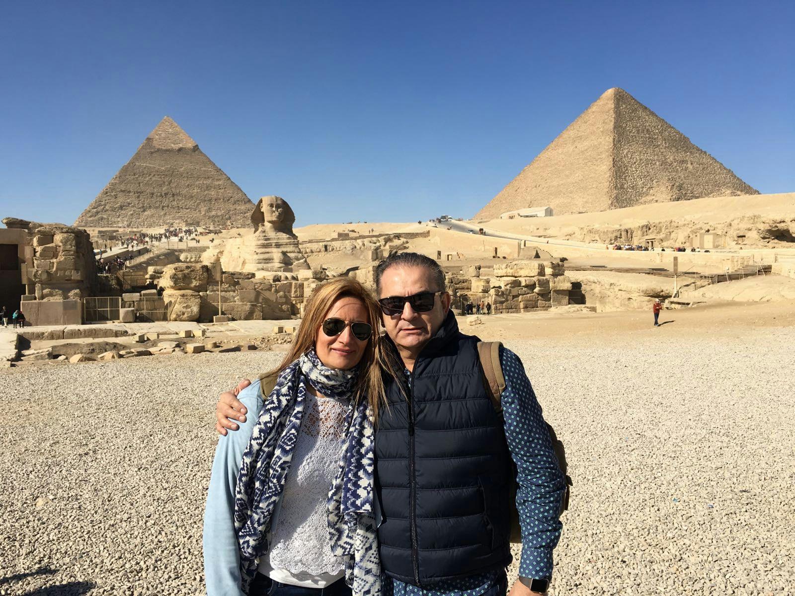 Nando y Tina en la explanada de Guiza con la esfinge y las piramides al fondo.