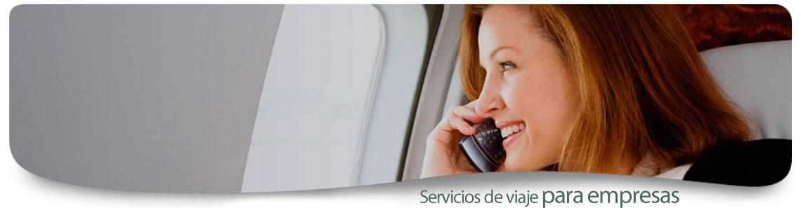 Mujer de negocios vestida con traje negro y camisa blanca viajando cómodamente en avión mientras habla por teléfono